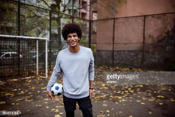 Lächelnde Spieler Fußball Kugel steht auf Straße