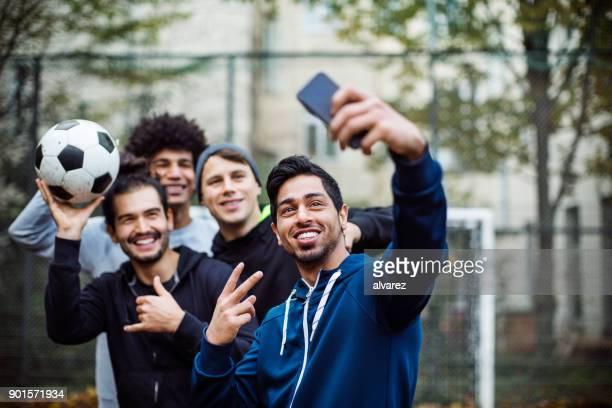 Smiling players taking selfie through mobile phone