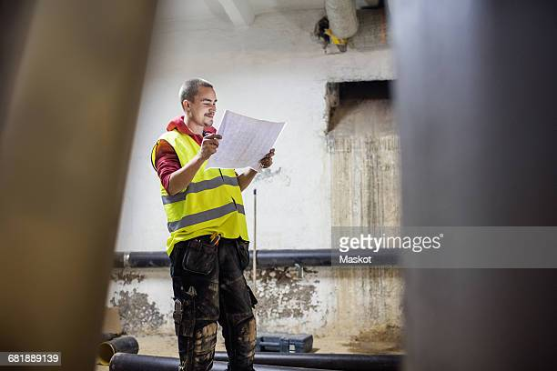 Smiling plumber reading document while standing by pipes in basement