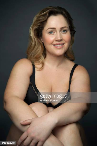 Smiling plus size woman in her late thirties wearing black lingerie in front of a dark gray background while hugging her knees and showing some cleavage.