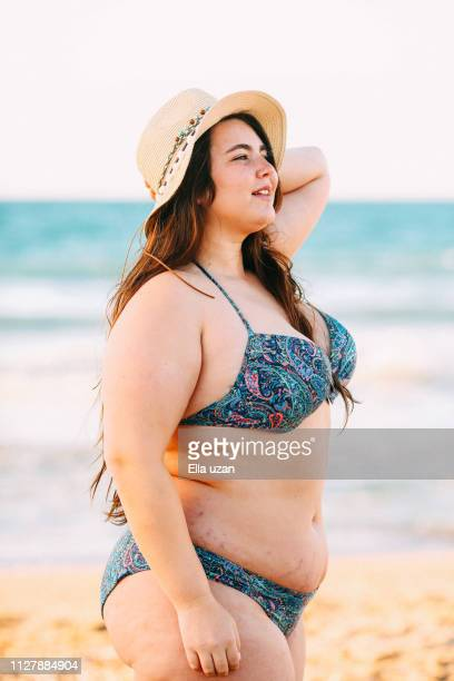 smiling Plus woman wearing summer hat on the beach