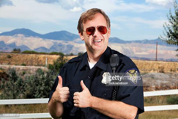 Smiling policeman thumbs up with sunglasses