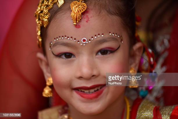 A smiling Portrait of a Nepalese young girl impersonate as a Kumari or living Goddess participate in the ritual during celebration of Kumari puja at...