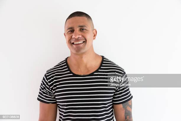 A smiling portrait of a pacific Island Man against a white background