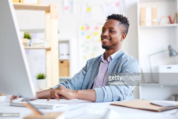 smiling positive young african creative graphic designer with beard using modern computer while creating maquette and sitting at table - graphic designer stock pictures, royalty-free photos & images