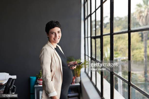 smiling pregnant businesswoman standing in office - cream coloured blazer stock pictures, royalty-free photos & images