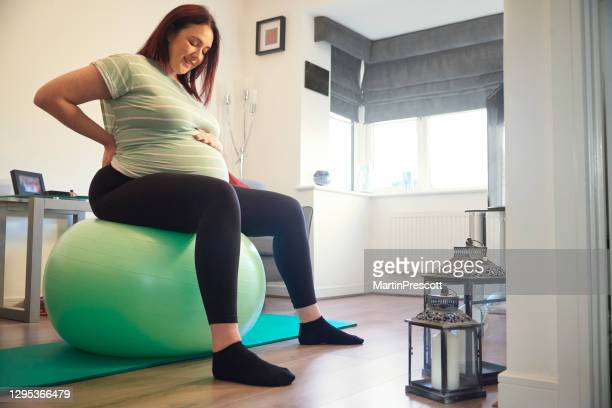smiling pregnant lady on gym ball - human back stock pictures, royalty-free photos & images