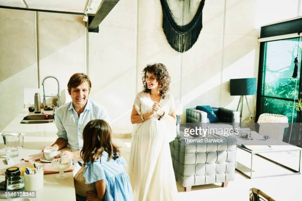 smiling pregnant mother and father hanging out with young daughter in home - maternity wear stock pictures, royalty-free photos & images