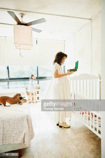 smiling pregnant mother looking at music box while preparing nursery for baby - music box stock pictures, royalty-free photos & images