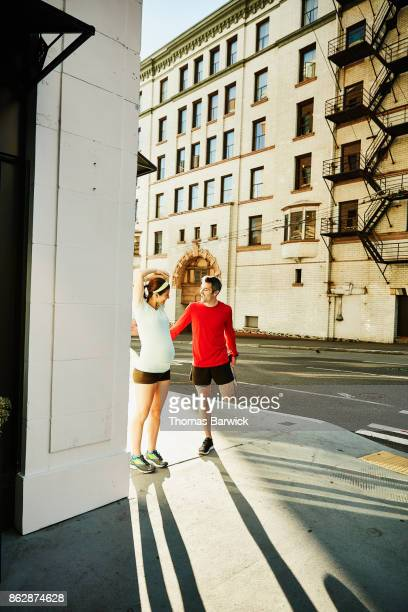 Smiling pregnant woman and husband stretching together before early morning run