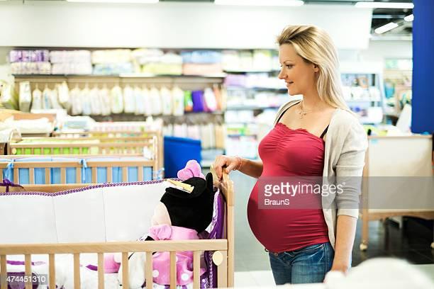Souriant femme enceinte choisir un lit bébé dans un magasin.