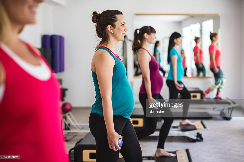 Smiling pregnant woman doing prenatal Pilates exercises in health club. : Stock Photo