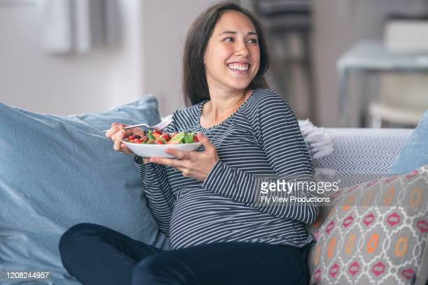 smiling pregnant woman eating salad - maternity wear stock pictures, royalty-free photos & images