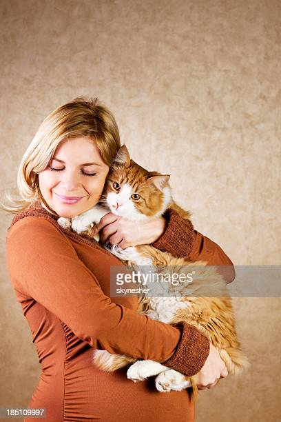 Smiling pregnant woman holding her cute cat