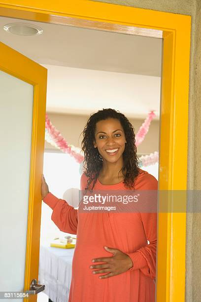 Smiling pregnant woman in doorway