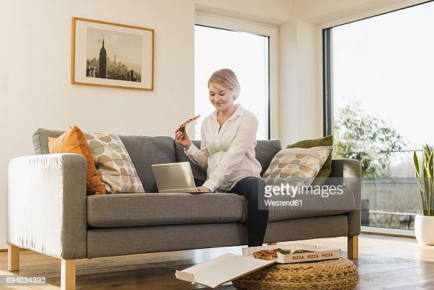Smiling pregnant woman on couch holding a slice of pizza using laptop
