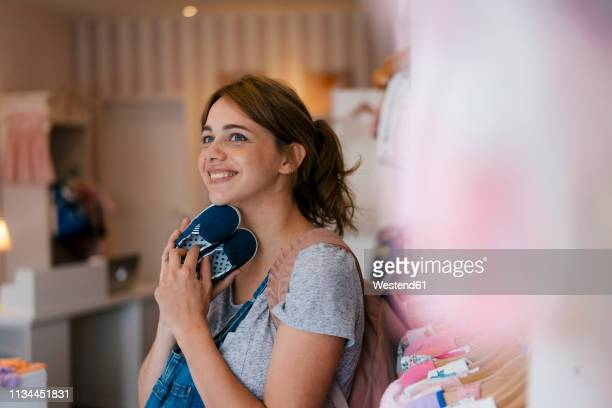 smiling pregnant woman shopping for baby clothing in a boutique - babybekleidung stock-fotos und bilder