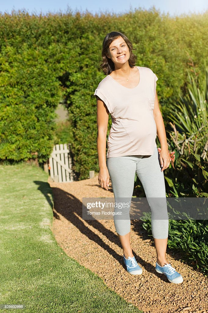 Smiling pregnant woman standing on path in garden : Foto de stock