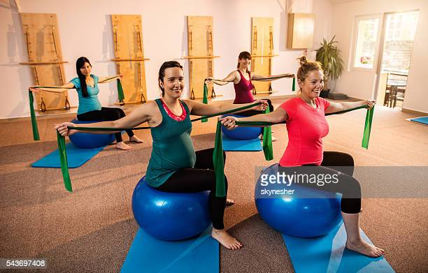 Smiling pregnant women on fitness balls doing stretching exercises.