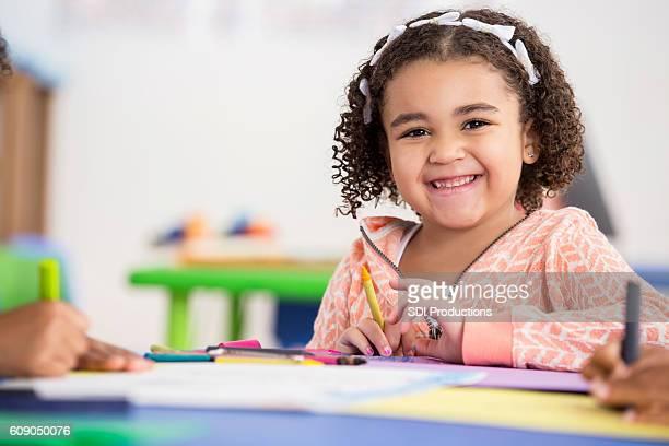 Smiling preschool girl has fun in her class
