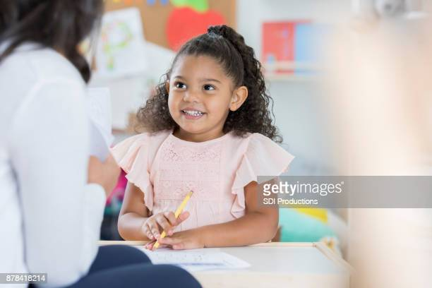 Smiling preschooler talks with teacher