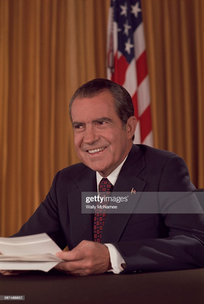 A smiling President Richard M. Nixon prepares to deliver a speech from the Oval Office at the White House. 1969.