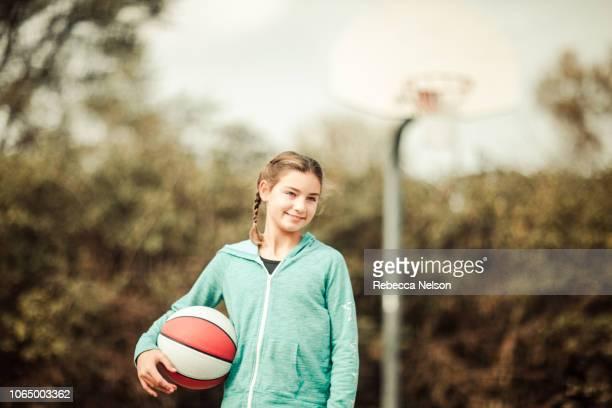 smiling pre-teen girl holding basketball on outdoor basketball court