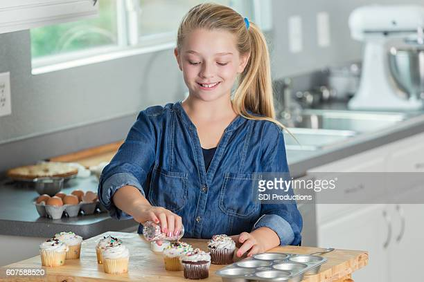 Smiling preteen girl using sprinkles to decorate cupcakes