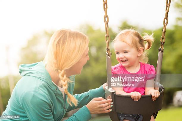 Smiling pretty toddler girl on swing