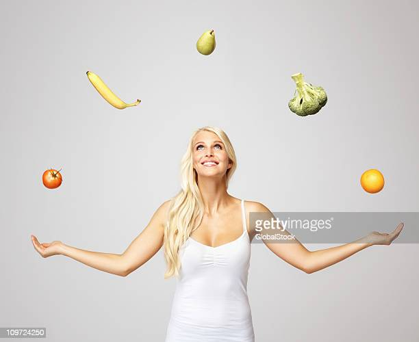 Smiling pretty woman juggling fruits and vegetables