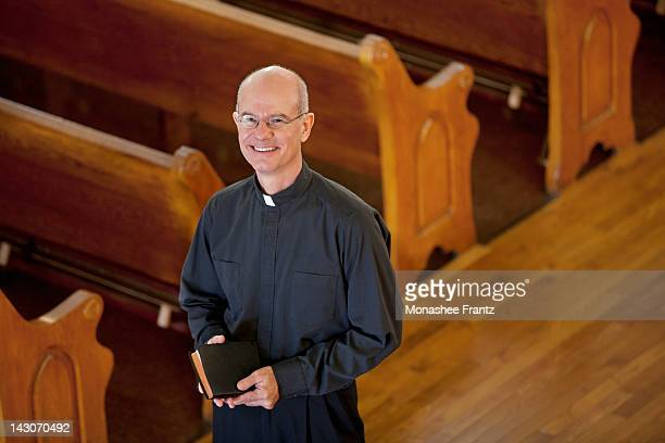 smiling priest standing in church - priest stock pictures, royalty-free photos & images