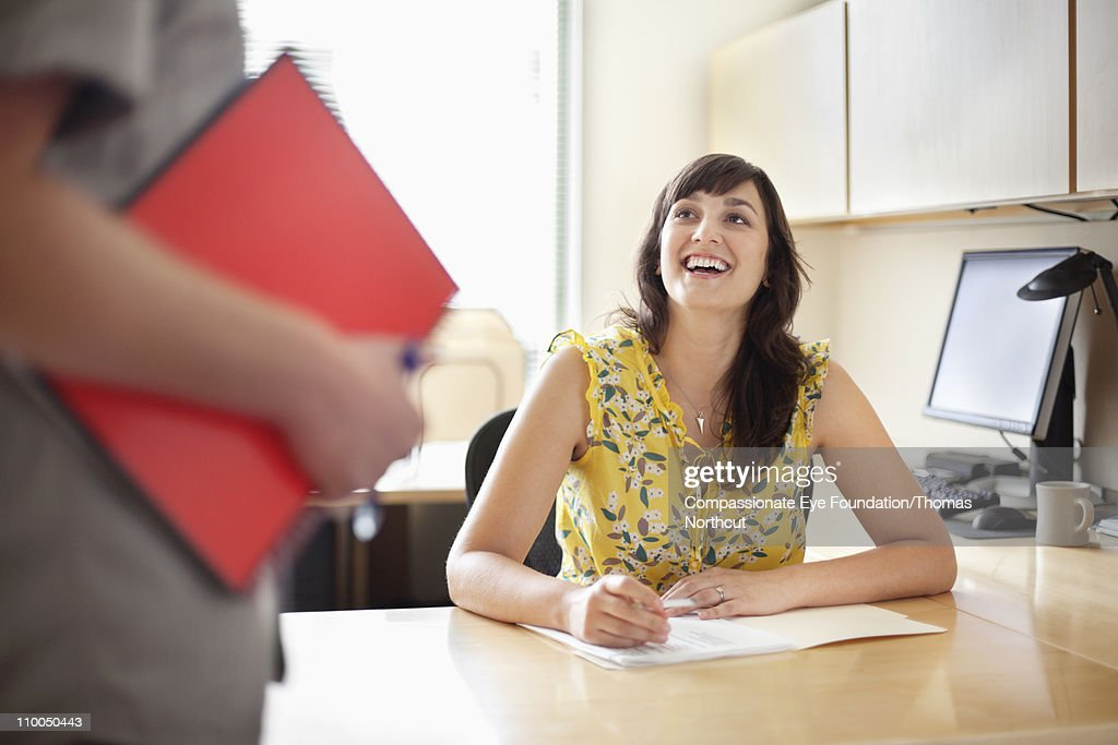 Smiling professional woman sitting at a desk : Stock Photo