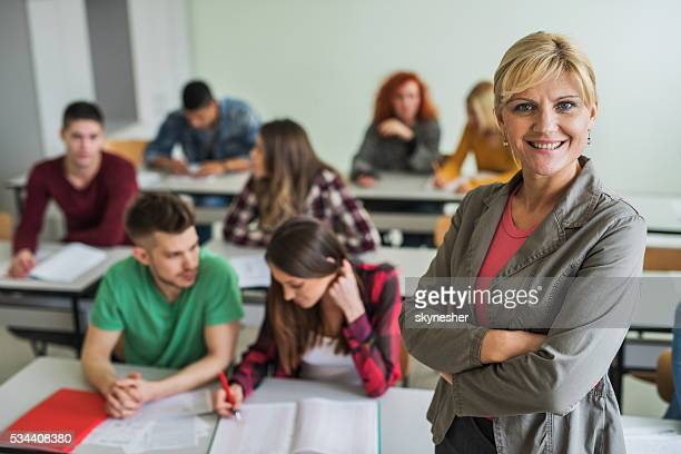 Smiling professor with arms crossed standing in the classroom.
