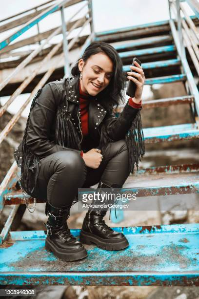 smiling punk female using smartphone while sitting on metal staircase outside - punk music stock pictures, royalty-free photos & images