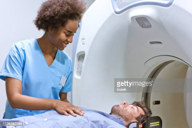 smiling radiologist preparing man for mri scan - cat scan machine stock pictures, royalty-free photos & images