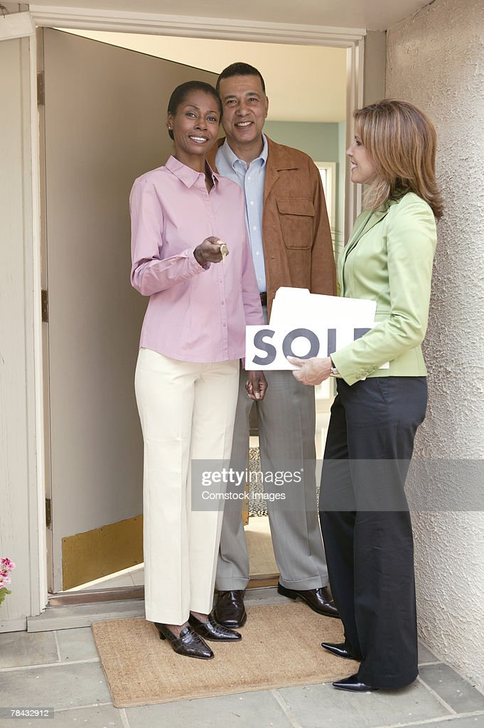 Smiling realtor with couple at new home : Stockfoto