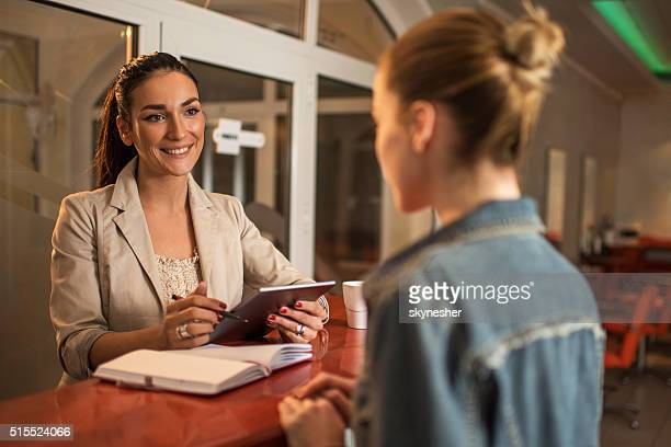 Smiling receptionist talking to customer in beauty salon.