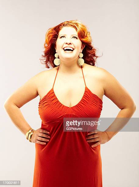smiling red-haired woman wearing red dress - big fat white women stock pictures, royalty-free photos & images