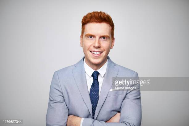 smiling redhead businessman with arms crossed - anzug stock-fotos und bilder