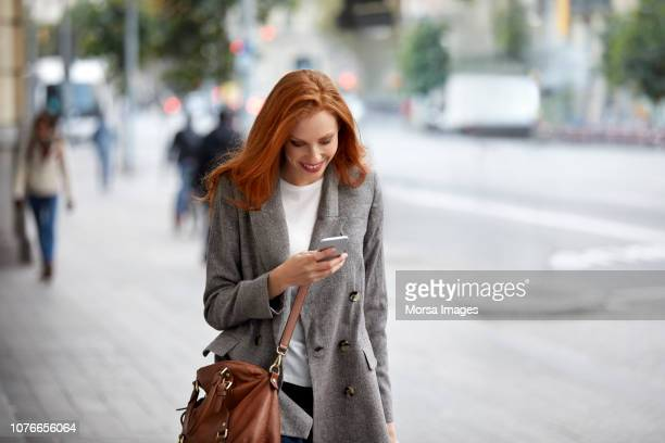 smiling redhead female commuter using smart phone - gray coat stock pictures, royalty-free photos & images