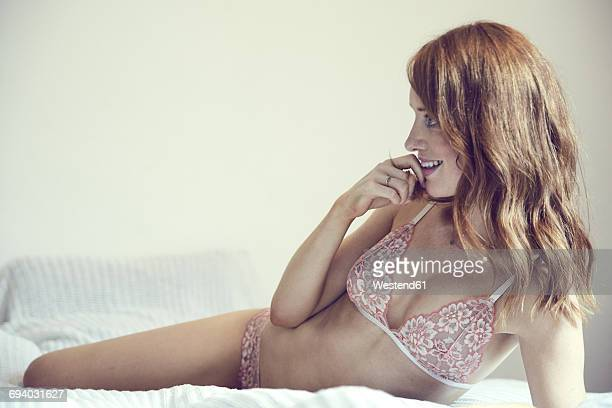 Smiling redheaded woman wearing lingerie lying on bed