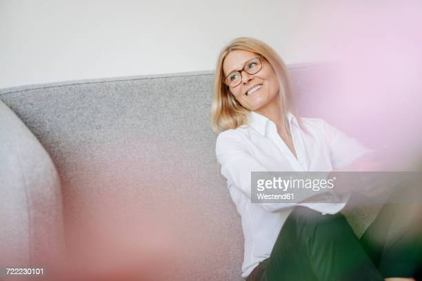 Smiling relaxed businesswoman sitting on couch