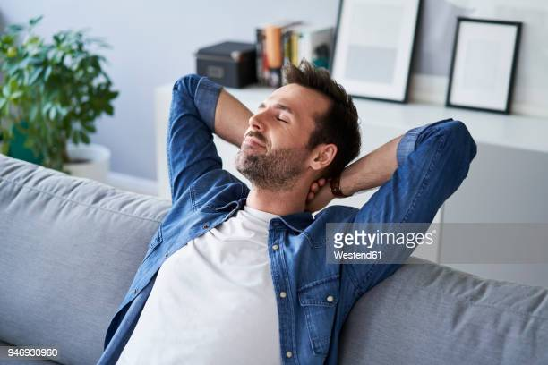 smiling relaxed man sitting on sofa daydreaming - temps libre photos et images de collection