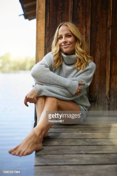 smiling relaxed woman sitting on wooden jetty at a lake - shorts stock-fotos und bilder