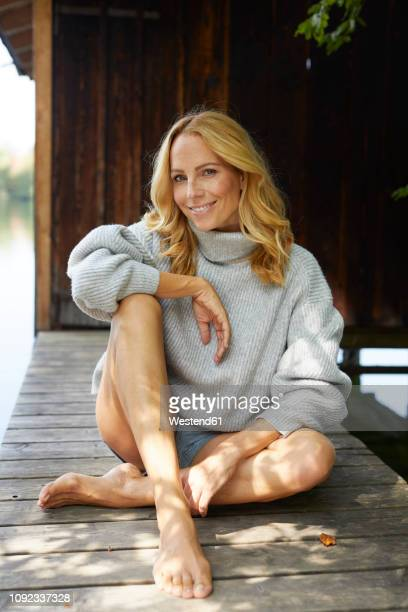 smiling relaxed woman sitting on wooden jetty at a lake - leg stock pictures, royalty-free photos & images