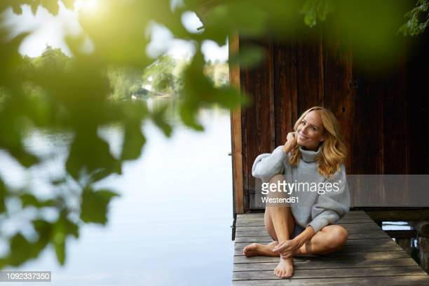 smiling relaxed woman sitting on wooden jetty at a remote lake - older woman legs stock photos and pictures