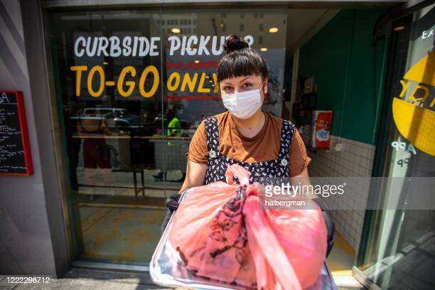 smiling restaurant worker wearing mask during covid-19 lockdown holding out to-go order to camera - curbside pickup stock pictures, royalty-free photos & images