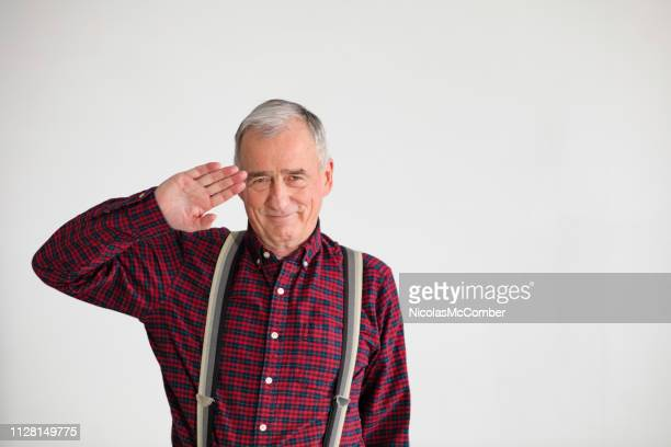 smiling retired army officer in his late 70s studio portrait saluting - checked pattern stock pictures, royalty-free photos & images