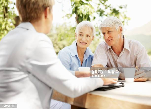 Smiling retired couple with a female banking agent