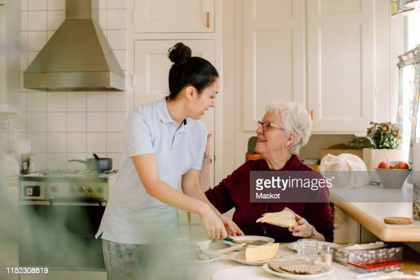 smiling retired elderly woman talking with female caregiver in kitchen at nursing home - zorg stockfoto's en -beelden